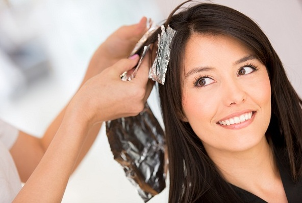 Brunette woman dying her hair at the beauty salon